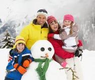 Familien-Gebäude-Schneemann am Ski-Feiertag lizenzfreie stockbilder