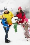 Familien-Gebäude-Schneemann am Ski-Feiertag Stockbild