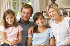 Familien-Gruppe, die auf Sofa Indoors sitzt Stockfotografie