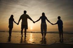Familien-Holding-Hände auf dem Strand, der den Sonnenuntergang überwacht Lizenzfreie Stockfotografie