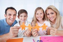 Familien-Holding-Papier-Leute in der Hand Lizenzfreies Stockfoto