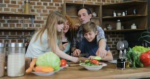 Familien-Kommunikation während zusammen kochen in den Küchen-Eltern mit zwei Kindern, die zu Hause Lebensmittel das Hacken sprech stock video footage