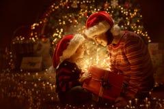 Familien-offenes Weihnachten, das anwesende Geschenkboxfront von Weihnachtsbaum, glückliche Mutter mit Baby beleuchtet stockfotos