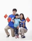 Familien-Porträt, ein Kind mit Eltern, wellenartig bewegende chinesische Flaggen, Atelieraufnahme Lizenzfreies Stockbild
