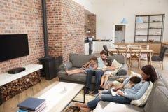 Familien-Sit On Sofa In Open-Plan-Aufenthaltsraum unter Verwendung der Technologie stockfotos
