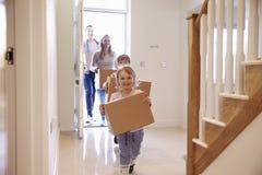 Familien-tragende Kästen in neues Haus an beweglichem Tag