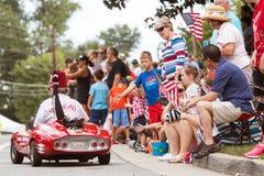 Familien-Wellen-amerikanische Flaggen an der alten Soldat-Tagesparade Lizenzfreie Stockfotografie