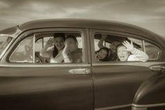 Familien-wellenartig bewegendes hallo im Weinlese-Auto Stockbild