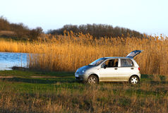 Familienauto am Flussufer, in der Sonnenuntergangleuchte Lizenzfreies Stockfoto