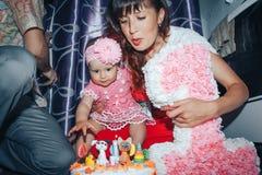 Familienbestehenvater, -mutter und -tochter feiern Geburtstag des einjährigen Mädchens stockfotos