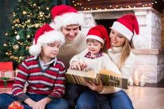 Familienblick auf Fotoalbum zusammen nahe Weihnachten Lizenzfreie Stockbilder