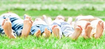 Familienfüße auf Gras Stockbild
