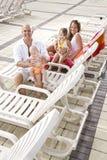 Familienferien, entspannen sich auf Poolplattform-Aufenthaltsraumstühlen Stockbild