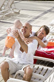 Familienferien, entspannen sich auf Poolplattform-Aufenthaltsraumstühlen Lizenzfreies Stockbild
