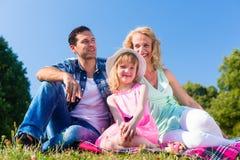 Familienfoto mit Vater, Mutter und Tochter in der Wiese Stockfotografie