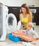 Familienfrau, die herein Kleidung zur Waschmaschine setzt Lizenzfreies Stockfoto