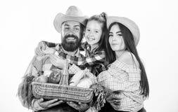 Familiengartenarbeit Eltern und Tochterlandwirte feiern Erntefeiertag Familienbauernhofkonzept Familienlandwirte umarmen Griff stockfoto