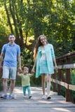 Familienhändchenhalten mit zierlicher Tochter im Sommer parkt stockfotos