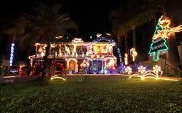 Familienhaus verziert mit Weihnachtslichtern und -dekorationen Stockbild