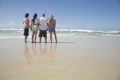 Familienholdinghände auf dem Strand Stockbilder