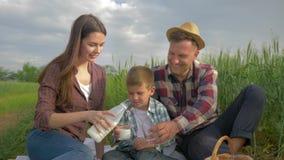 Familienidylle, glückliche Frau gießen Milch in Gläser zum Kinderjungen und zu lächelndem Mann im Hut bei auf Picknick draußen si stock video