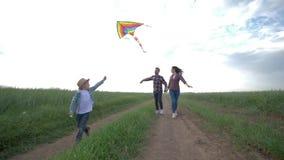 Familienidylle, kleiner Junge mit Drachen in seinen H?nden laufen auf Landschaft in der Zeitlupe auf Hintergrund von jungen Elter stock video