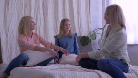 Familienidylle, -mutter und -töchter, die beim Sitzen auf Bett plaudern und sich umarmen stock footage
