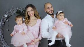 Familienidylle, -mutter und -vati, die für Foto mit Töchtern auf Armen auf Hintergrund der grauen Wand mit dekorativem Kranz aufw stock video