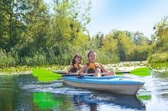 Familienkayak fahren, -mutter und -tochter, die im Kajak auf dem Flusskanuausflug hat Spaß, aktives Herbstwochenende schaufelt Lizenzfreies Stockfoto
