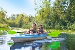 Familienkayak fahren, -mutter und -tochter, die im Kajak auf dem Flusskanuausflug hat Spaß, aktives Herbstwochenende schaufelt Lizenzfreie Stockfotografie