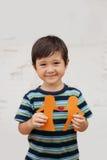 Familienkonzept mit dem kleinen Jungen, der Papierkette hält, formte wie ein traditionelles Paar mit Herzen Stockbilder