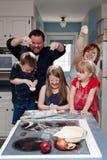 Familienlebensmittelkampf in der Küche stockfotografie