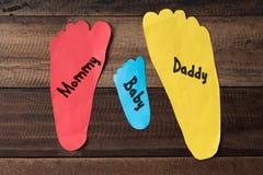 Familienmaß ihre Füße mit buntem Papier auf hölzernem Hintergrund stockbilder