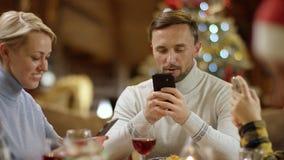 Familienmitglieder, die das Internet auf Smartphone durch Christmsa-Tabelle, Abschluss oben auf jungem Mann surfen stock video
