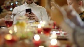 Familienmitglieder, die das Internet auf Smartphones durch Weihnachtstabelle, Abschluss oben auf jeder Hände surfen stock video