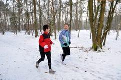 Familienmitglieder, die in den Schnee laufen stockfotos