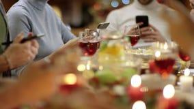 Familienmitglieder, die Smartphones durch Weihnachtstabelle, Abschluss oben auf jeder Hände verwenden stock video footage
