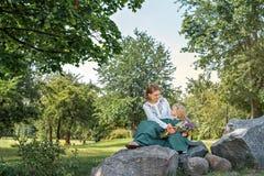 Familienmutter mit Tochter im Weinleseretrostilleinen kleidet das Sitzen auf einem Stein im Parkwald mit Blumenstrauß von Blumen  stockbild