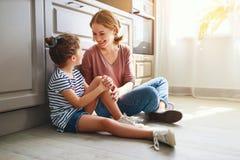 Familienmutter und Kindertochter, die in der K?che auf Boden umarmt lizenzfreies stockbild