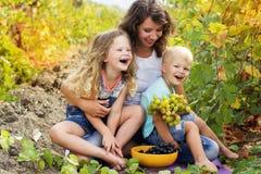 Familienmutter und zwei childs im Traubenweinberg Lizenzfreie Stockfotos
