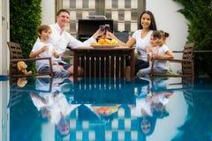 Familiennehmenabendessen zusammen am Pool lizenzfreies stockfoto