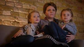 Familienporträt der kaukasischen Mutter mit zwei Töchtern, die sich umarmen und in der angenehmen Hauptatmosphäre in Verbindung s stock video footage