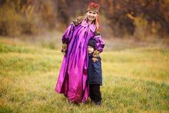 Familienporträt der Mutter mit ihrem Sohn draußen im traditionellen nationalen Kostüm Herbstfarben, asiatische Verzierungen lizenzfreie stockbilder