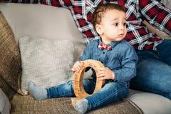 Familienporträt des kleinen Kindes in den Jeans, die nahe zu Hause zum Wohnzimmer des Vaters sitzen Lizenzfreie Stockbilder