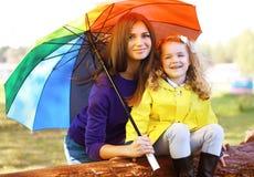 Familienporträtmutter und -kind mit buntem Regenschirm Stockfoto