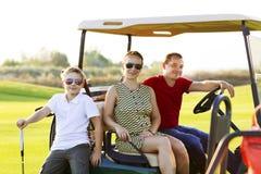 Familienporträt in einem Warenkorb am Golfplatz Lizenzfreie Stockfotos