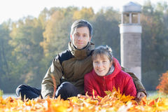 Familienporträt im Freien von zwei jungen erwachsenen Leuten im Herbst parken Hintergrund Stockfotografie