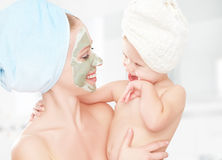 Familienschönheitsbehandlung im Badezimmer Mutter- und Tochterbaby machen eine Maske für Gesichtshaut Stockbilder