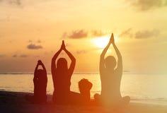 Familienschattenbilder, die Yoga bei Sonnenuntergang tun Stockfoto