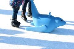 Familienspaß auf Eisbahn im Freien, Kind, das lernt, mit Plastikdichtung als Ausbildungshilfen eiszulaufen Lizenzfreie Stockfotografie